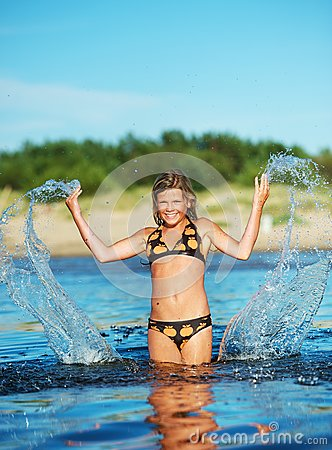 Happy girl making water splashes