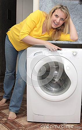 Happy girl near wash mashine