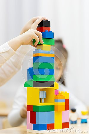 Happy girl playing with colorful building blocks in a nursery room Stock Photo