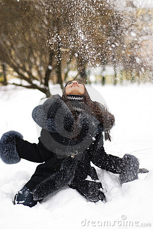 Happy girl playing with snow