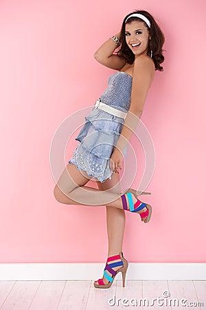 Happy girl posing in mini dress an high heels