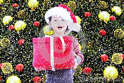 Happy girl receive christmas gift under tree