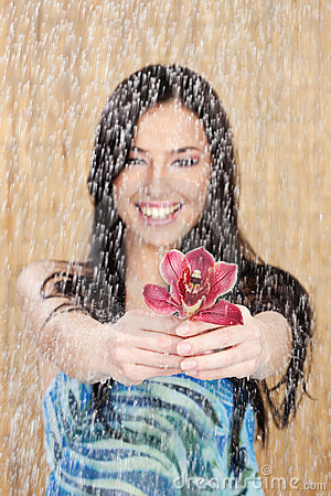 Happy girl with red orchid under water drops