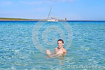 Happy girl relaxing in the crystal clear sea, La Pelosa, Sardinia, Italy