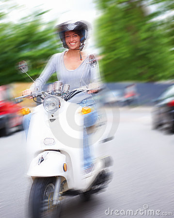 Happy girl riding a motorcycle on the street