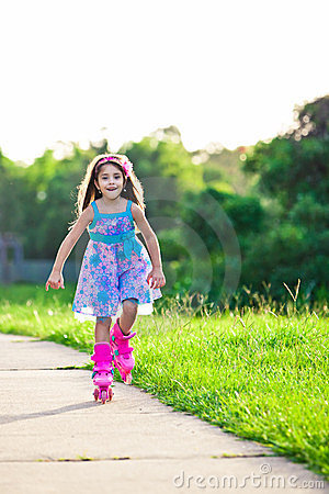 Happy girl riding on roller blades in the park