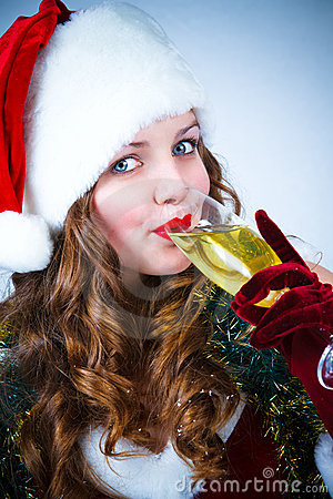 Happy girl in Santa Claus hat with champagne