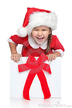 Happy girl in Santa hat looks out of gift box