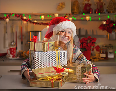Happy girl in santa hat with stack of christmas present boxes