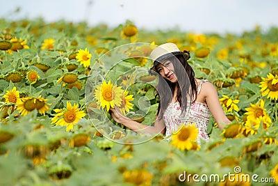 Happy girl between sunflower