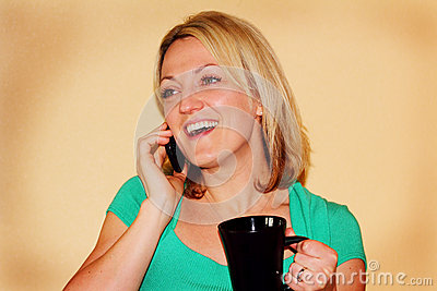 Happy girl talking on phone holding mug