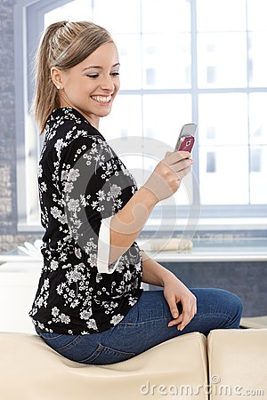 Happy girl texting on mobile at home