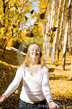 Happy girl throwing  leaves