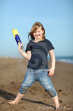 Happy girl with toy gun on the beach
