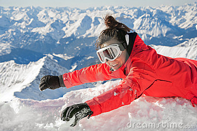Happy girl waving on snow on a mountain