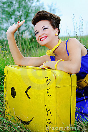 Happy girl with a yellow suitcase waving goodbye