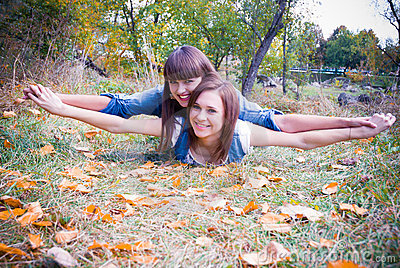Happy girls in autumn leaves