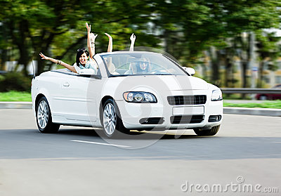 Happy girls in the cabriolet with arms outstretched