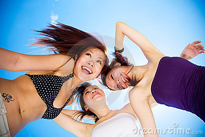 Happy girls friends having fun under bright blue sky