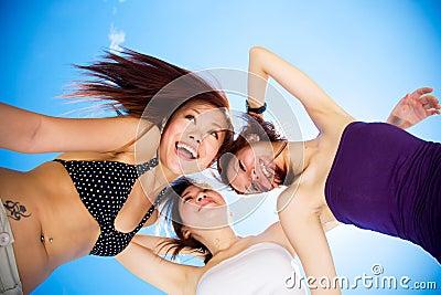 Happy girls friends having fun under bright blue sky
