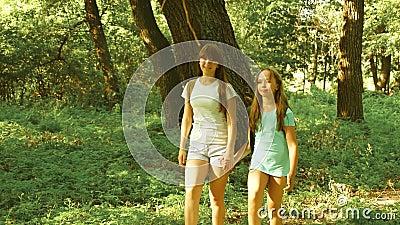 Happy-Girls-Reisende durchqueren den Wald mit Rucksäcken im Sonnenschein Kinder sind in der Sonne zelten gegangen stock video