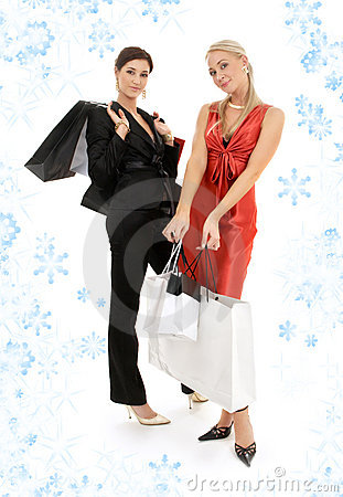 Happy girls with shopping bags and snowflakes
