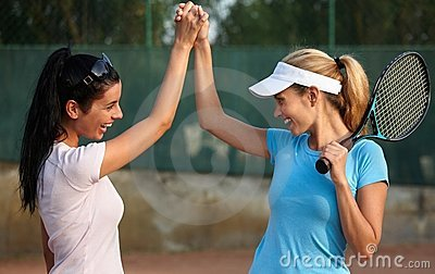 Happy girls on tennis court