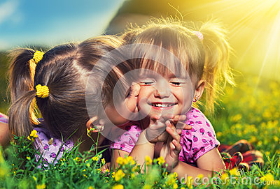 Happy girls twin sisters kissing and laughing in the summer