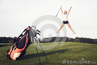 Happy golf player jumping on golf course.