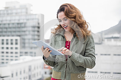 Happy gorgeous brunette in winter fashion using tablet