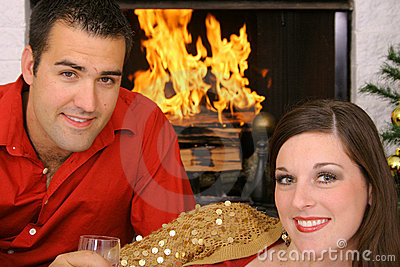 Happy gorgeous couple in front of fireplace