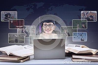 Happy graduate imagine online pictures on laptop