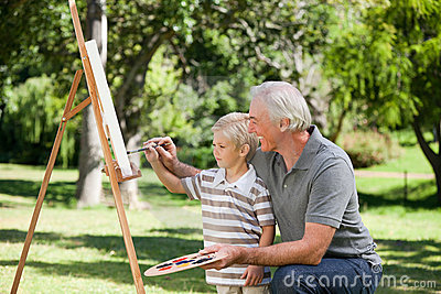 Happy Grandfather and his grandson painting