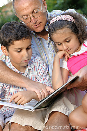 Happy grandfather and kids reading book