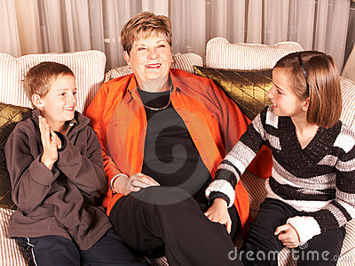 Happy grandmother and grandchildren on sofa