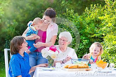 Happy grandmother having lunch with her family