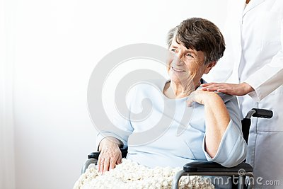 Happy grandmother in a wheelchair and caregiver supporting her. Stock Photo
