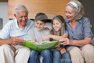 Happy grandparents and grandkids looking at album photo