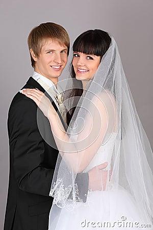Happy groom and bride embrace in studio