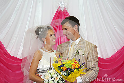 Happy groom and bride look at other