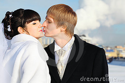 Happy groom and bride tender kiss at winter