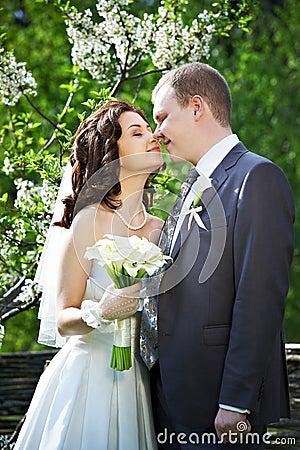 Happy groom and happy bride in spring garden