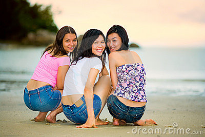 Happy group of woman at the sunset beach