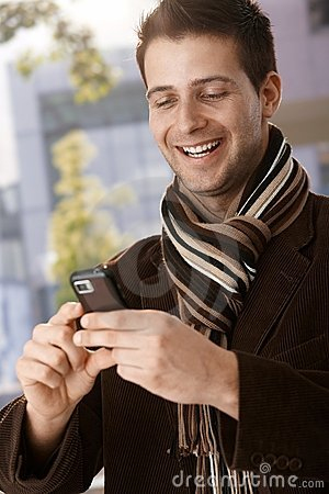 Happy guy looking at mobile phone