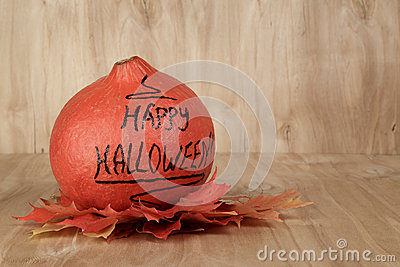 Happy Halloween inscription on the pumpkin with leaves