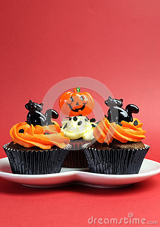 Happy Halloween orange and black decorated cupcakes - vertical with copyspace.