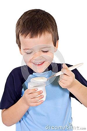 Happy healthy boy eating yogurt