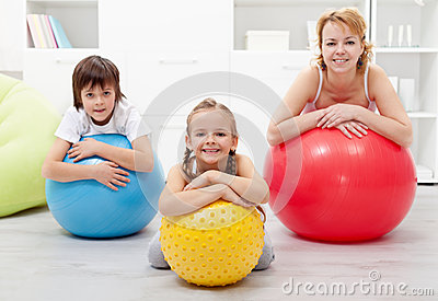 Happy healthy family relaxing in the middle of gymnastic exercis