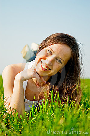 Happy healthy woman lying in the grass