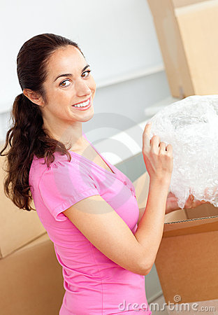 Happy hispanic woman unpacking boxes with glasses